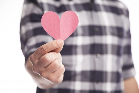 A man holds out a pink paper heart cut out of construction paper  Stock fotó