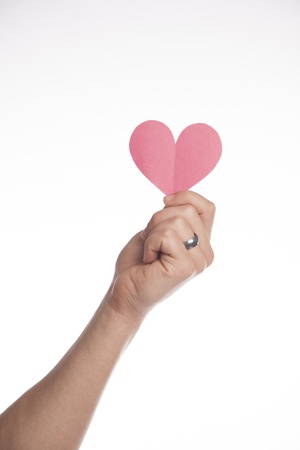 A man holds out a paper heart on a white background  photo