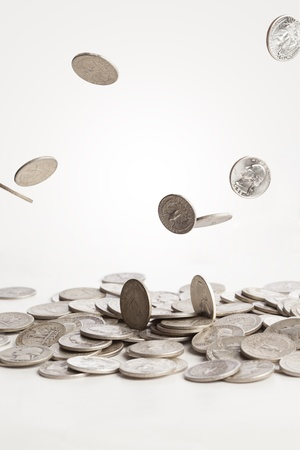 A group of silver coins are falling down into a pile of quarters