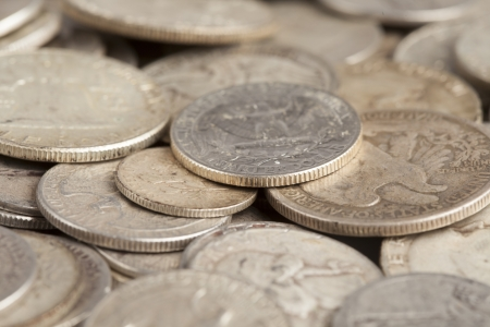 A quarter is shown close up on a pile of silver coins