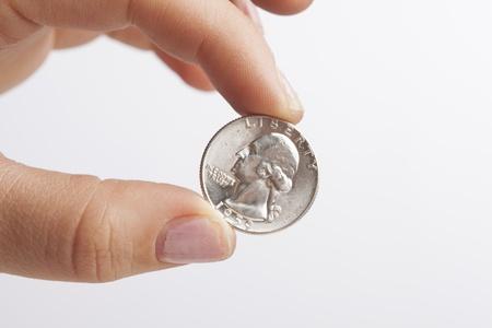 A close up of a hand holding a shiny silver quarter    photo