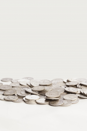 A group of shiny silver coins are shown on a white background Stock fotó