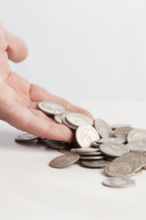 dropping: A pile of shiny money is dropping from a hand on a table    Stock Photo