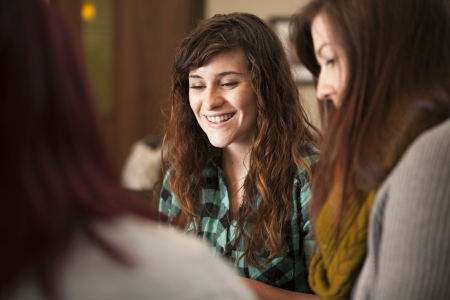 church group: A group of young women sit together and smile.