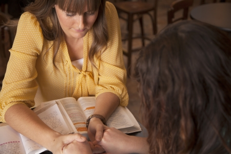 Two women hold hands and pray as they study the bible. Stock Photo
