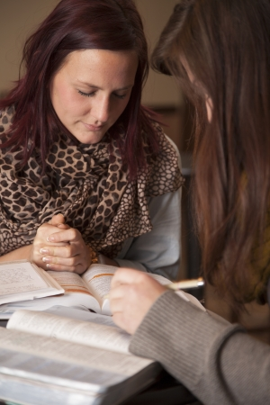 study group: Two beautiful young women bow their heads in prayer.
