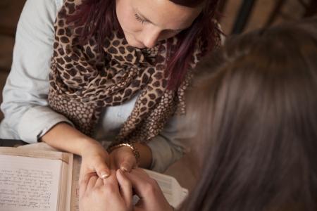leyendo la biblia: Dos mujeres j�venes toman de las manos y rezar durante un estudio de la Biblia.