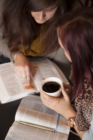 group study: Two young women study the bible together while drinking coffee.