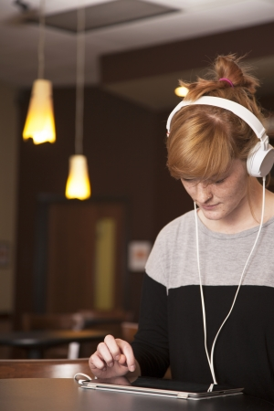 A young woman listens to music on her headphones with an electronic tablet.