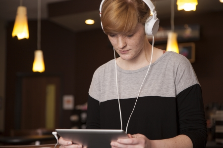 A young woman reads and listens while holding an electronic tablet. Stock Photo - 17850695