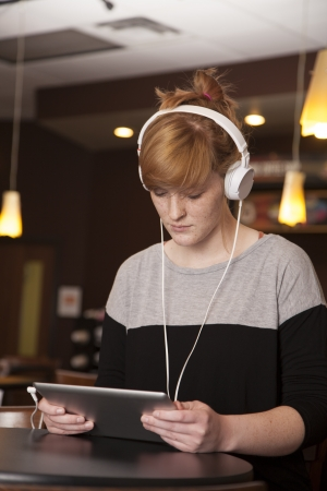 A young woman reads and listens while holding an electronic tablet.