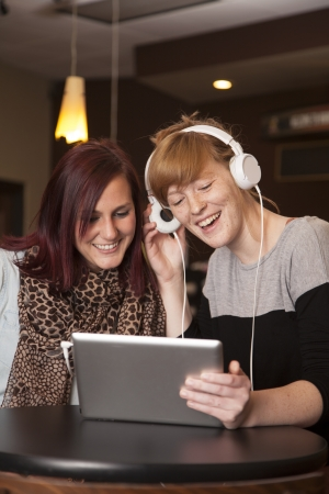 Two young women share headphones and listen to music on an electronic tablet. Stock fotó