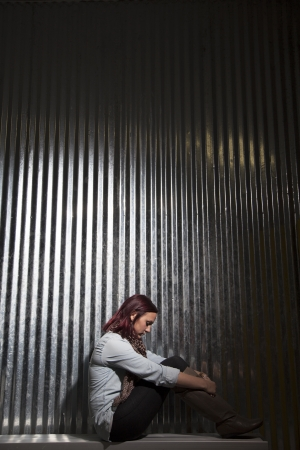A young woman sits alone in sadness against a metal wall. Stock fotó