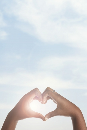 Woman holding her hands up in the shape of a heart around the sun   photo