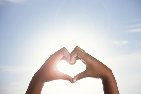 A woman holds her hands up to the sun in a heart shape