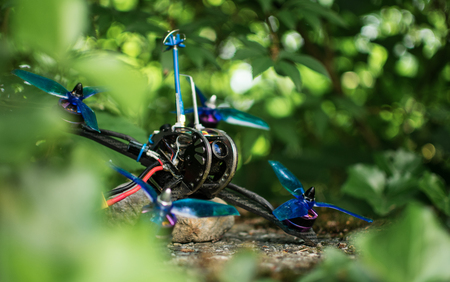Blue race drone for fpv first person view for racing with quadcopters with vibrant colors in nature green background.