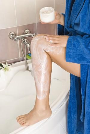 Woman rubbing cream on leg in bathroom photo