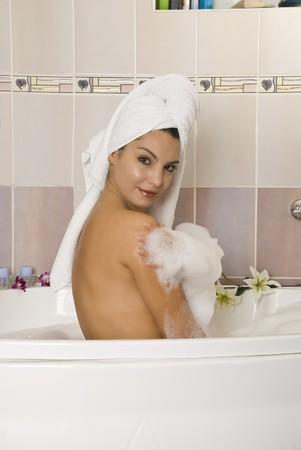 Beautiful woman in a bathtub with foam photo
