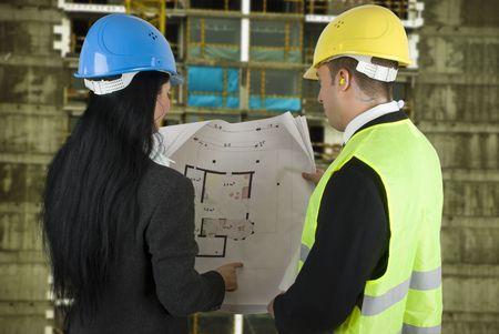 perito: Ingeniero en el sitio que muestra al comprador lo que el proyecto, ambos con casco protector