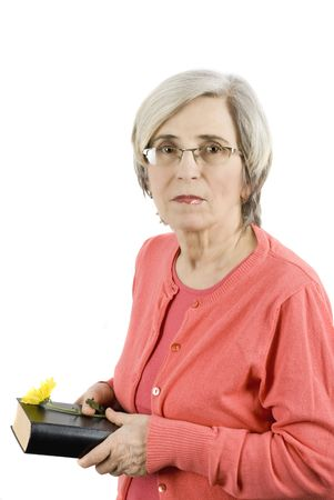 Mature woman holding a book and a yellow flower  photo