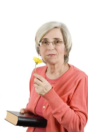Senior woman holding a bible and a yellow flower photo