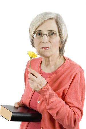 Attractive mature woman holding a book and smelling a yellow flower photo