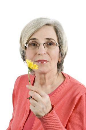 Portrait of beautiful senior woman holding a yellow flower photo