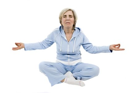 Mature woman doing yoga-lotus position dressed with a blue sport suit Stock Photo