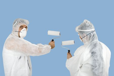 Painters couple with rollers paint on blue background