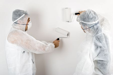 Two house painters dressed with protective outfit paint white wall