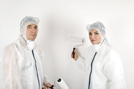 Two young painters with roller paint on white background