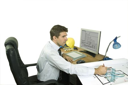 Young architect in office working at a project and using a laptop photo