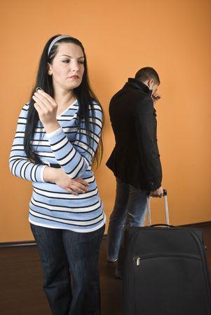 breakage: Mayor el divorcio, la mujer de pie con el anillo de boda en la mano y llorar y el hombre salir de la casa con el equipaje