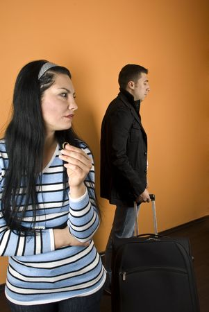 disillusioned: Divorce:Woman suffering , crying  and hold her wedding ring ,looking away  while the man leaves house with baggage