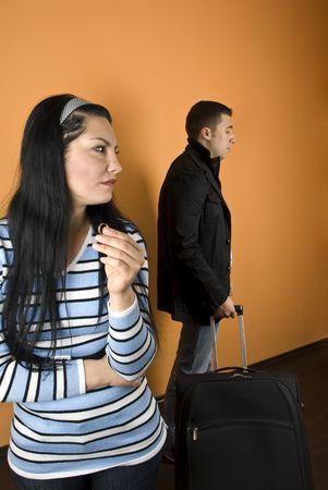 anillo de matrimonio: Divorcio: Mujer sufrimiento, el llanto y mantenga su anillo de bodas, en busca de distancia, mientras que el hombre deja la casa con el equipaje