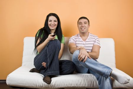 they are watching: Young happy couple on sofa watching TV , they change channels and have fun