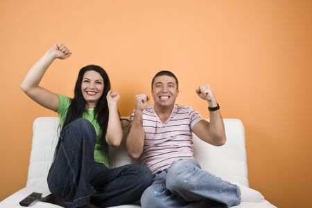 pareja viendo tv: Ventiladores joven feliz viendo la televisi�n su deporte favorito equipo Foto de archivo