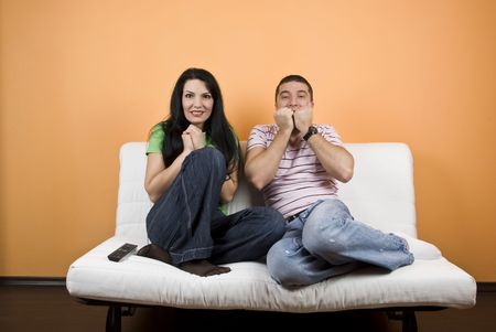 Young couple watching TV a scary movie at home photo