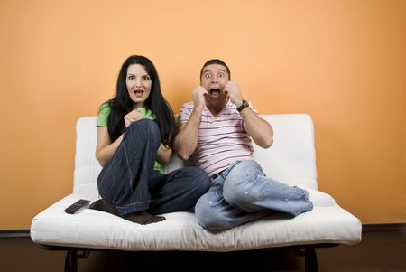 Young man and woman ,friends watching TV  a horror movie and they are scared  photo