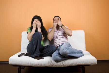 pareja viendo tv: Mayor viendo la televisi�n una pel�cula de horror, mujer cubrir los ojos para no ver nunca m�s, mientras que el joven est� aterrorizado