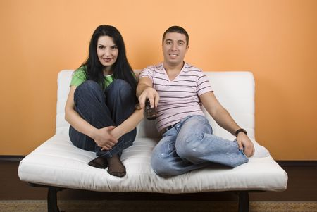 Cheerful young couple on white sofa watching TV photo