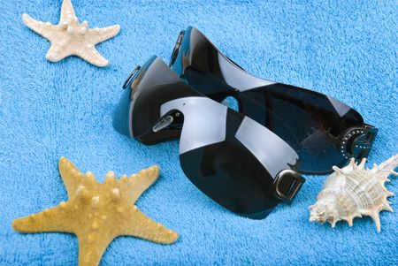 Close up of  two pairs of sunglasses and starfish on blue towel photo