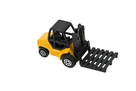 Yellow forklift toy used in manufacturing, industrial and commercial activity  isolated on white background photo