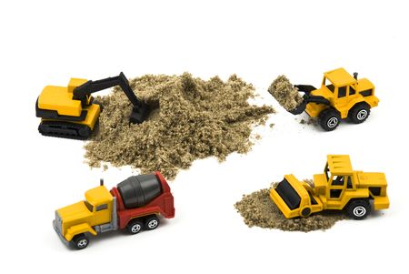 Trucks miniature working with sand isolated on white background photo