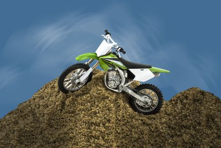 hillock: Single motorcycle toy  waiting on a sand hillock,abstract blue sky