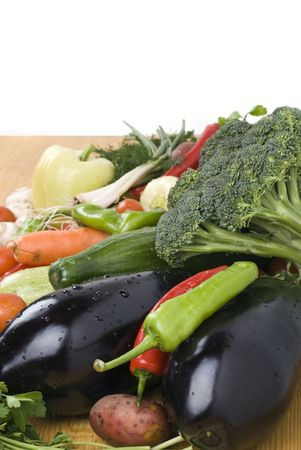 Fresh vegetables on wood table ,eggplants ,pepper and broccoli  in the foreground photo