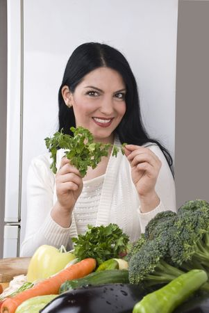 Happy young woman in kitchen holding fresh parsley in her hands and many vegetables on wood table photo