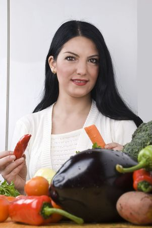 Young brunette woman in kitchen with fresh vegetables holding a red pepper and a carrot photo