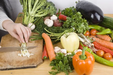 Close up of hand woman chopping  green onion on wood table in kitchen preparing dinner  photo