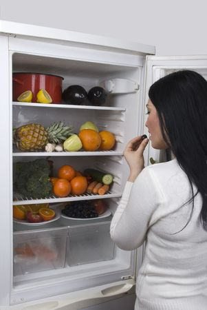 garden stuff: A young woman eating a grape berry from a full fridge with fresh fruits and vegetables